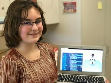 Alexandra Wyatt holds up a laptop with her snowman design.