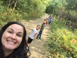 Picture of smiling Mrs. Walker and her first grade students in the China forest.