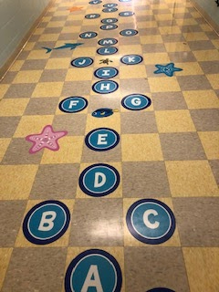 Picture of letters, fish and starfish on a checkered floor.